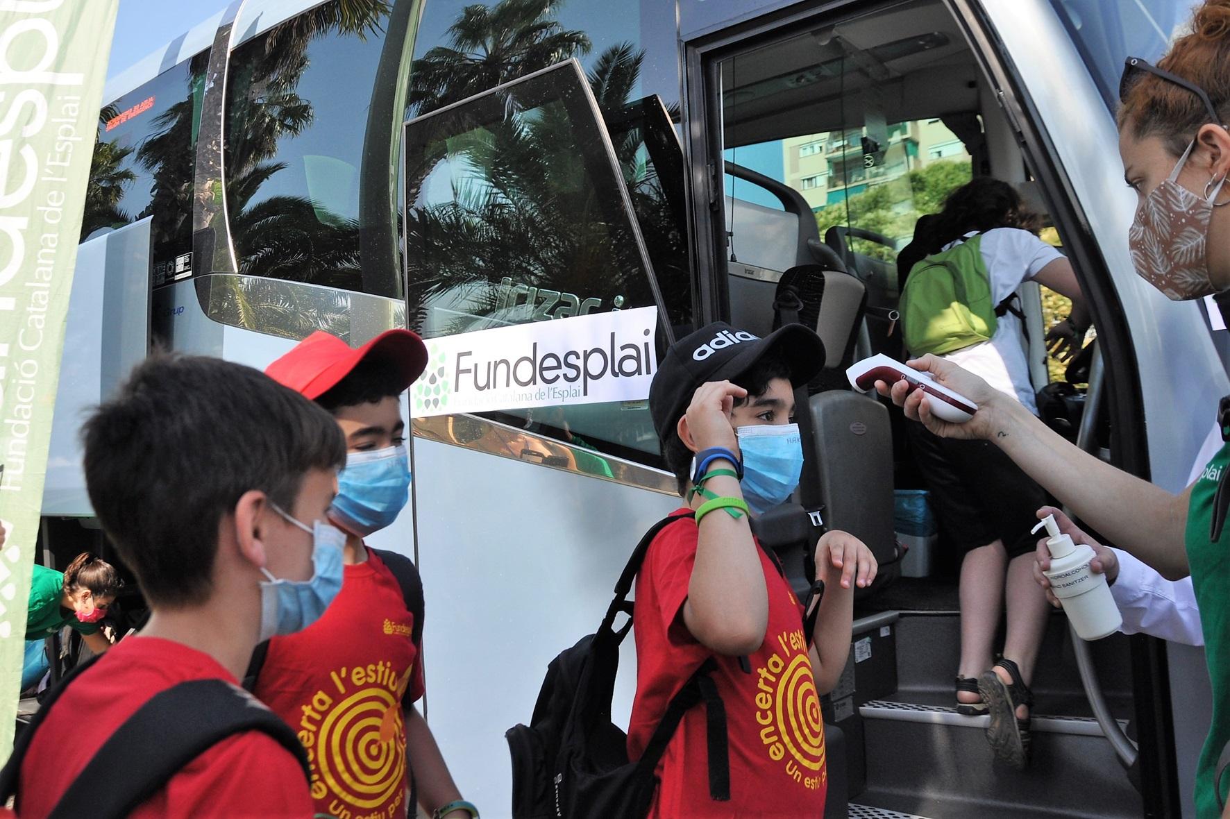 Imatge grup d'infants a l'entrada de l'autobús que els porta de colònies