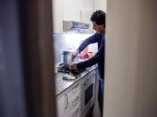Imatge persona atesa per Càritas Catalunya a la cuina de casa seva