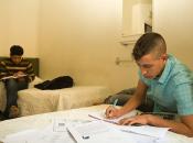 Imatge de dos joves migrats sols estudiant en un pis de suport