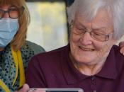dona gran amb un mòbil acompanyada per una altra persona